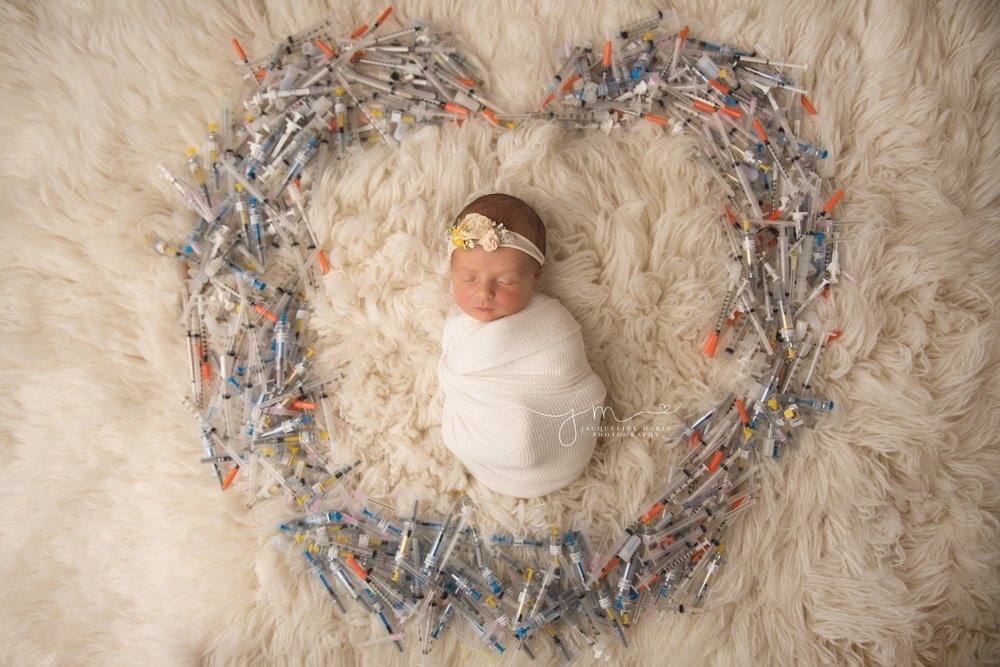 newborn baby girl in swaddled in cream wrap as IVF needles are placed in a heart around her in columbus ohio