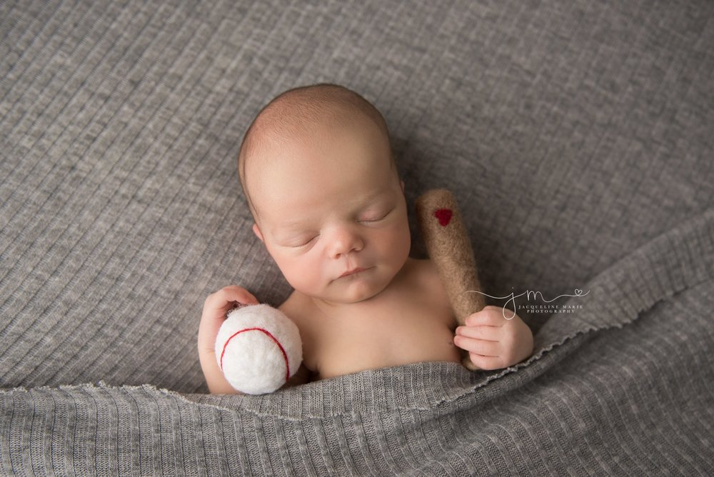 1 week old newborn baby boy holds felted baseball and bat for newborn photography pictures in columbus ohio