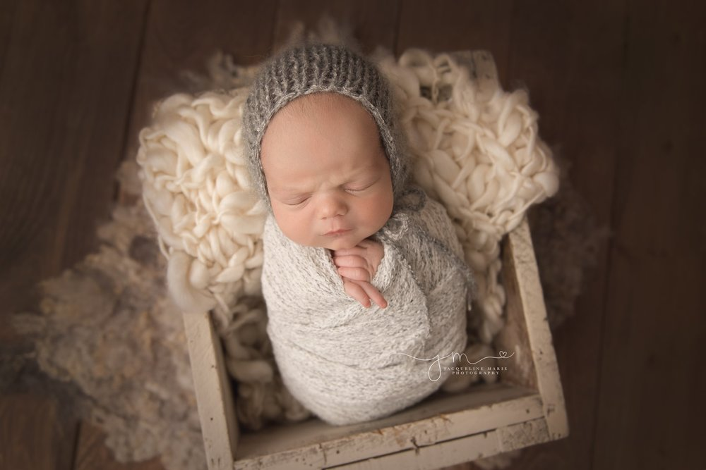 newborn baby boy is swaddled in gray wrap and matching bonnet in columbus ohio for newborn pictures