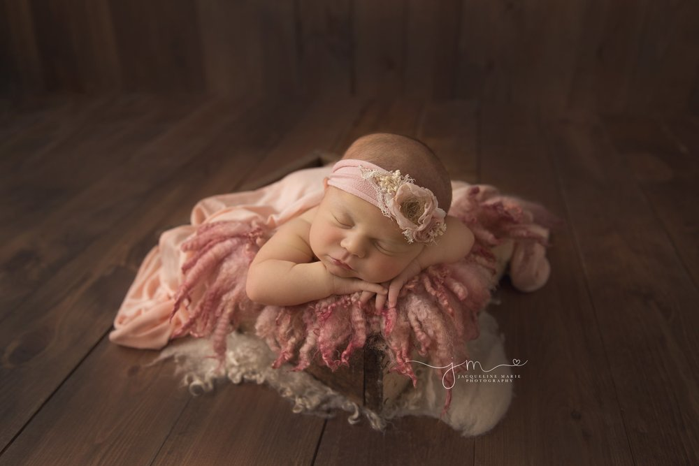 columbus ohio newborn photographer features image of baby girl on wood floor and pink headband