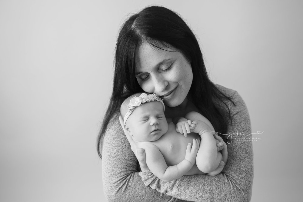 mother snuggles 1 week old newborn baby girl and smiles for newborn pictures in columbus ohio