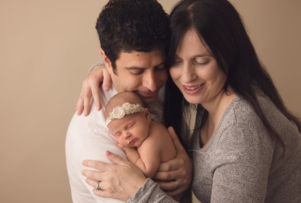 mother and father hold 1 week old baby girl in columbus ohio for newborn photography pictures
