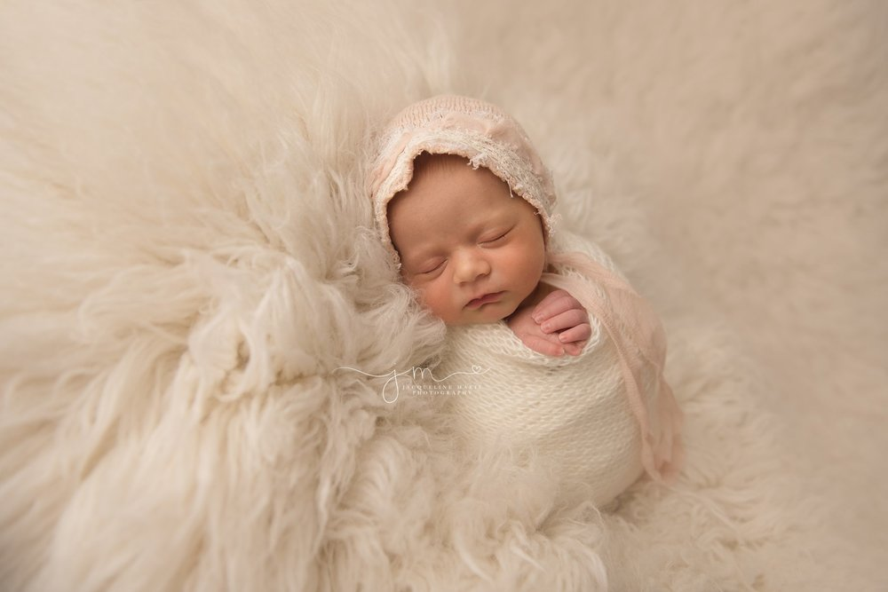 columbus ohio newborn photographer features image of newborn baby girl in pink bonnet