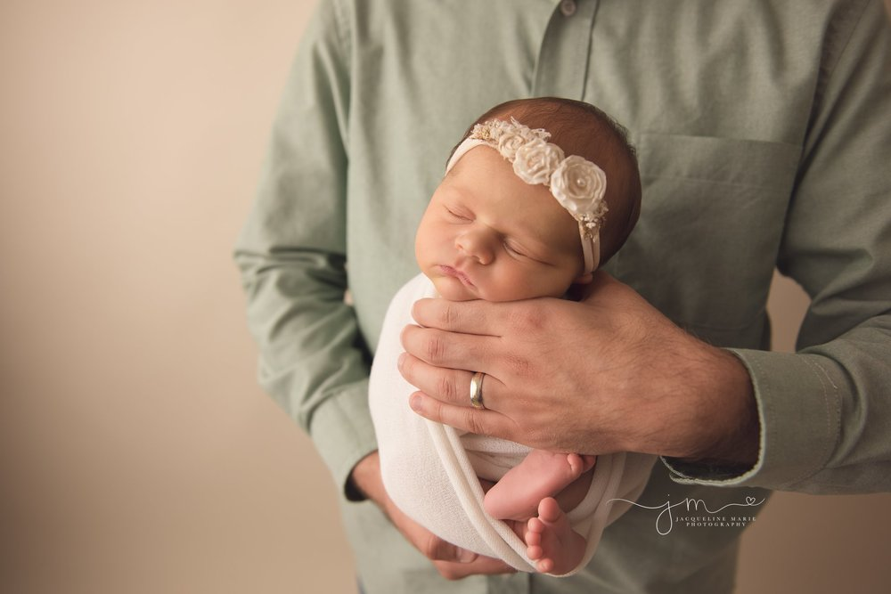 father holds newborn baby girl swaddled in cream wrap in columbus ohio