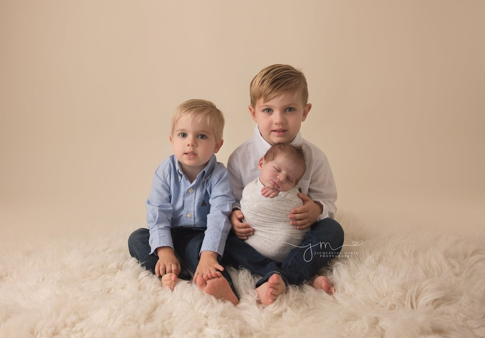 columbus ohio newborn baby boy is held by older brothers during newborn photography session