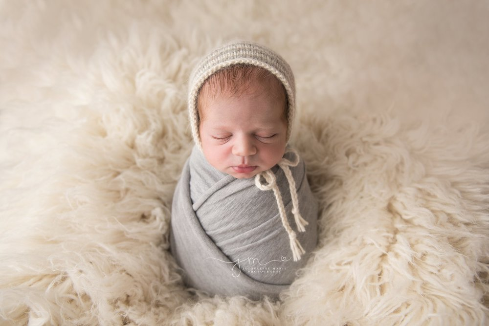 1 week old newborn baby boy is swaddled in gray wrap and cream stripe bonnet for newborn pictures in columbus ohio