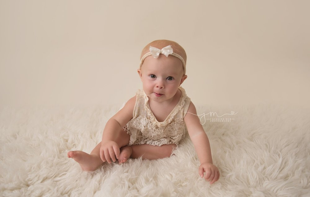 1 year old girl wears cream lace romper for first birthday pictures in columbus ohio