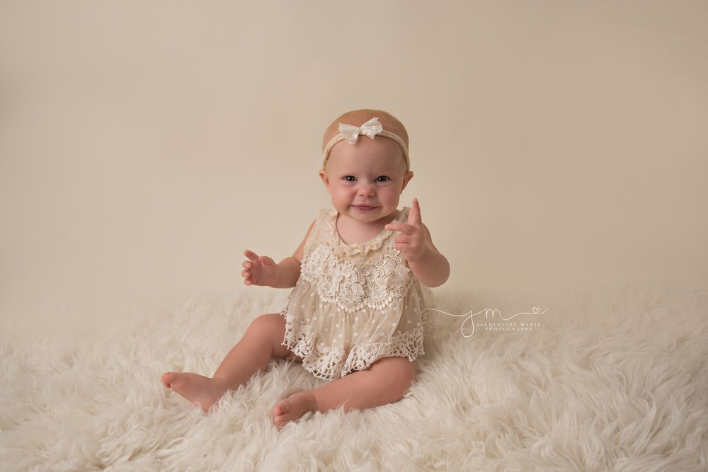 1 year old baby girl smiles on cream rug for first birthday photo session in columbus ohio