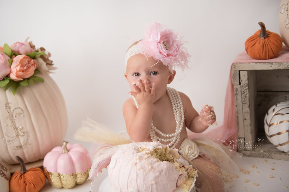 scarlett eats pink pumpkin cake for cake smash birthday pictures in columbus ohio