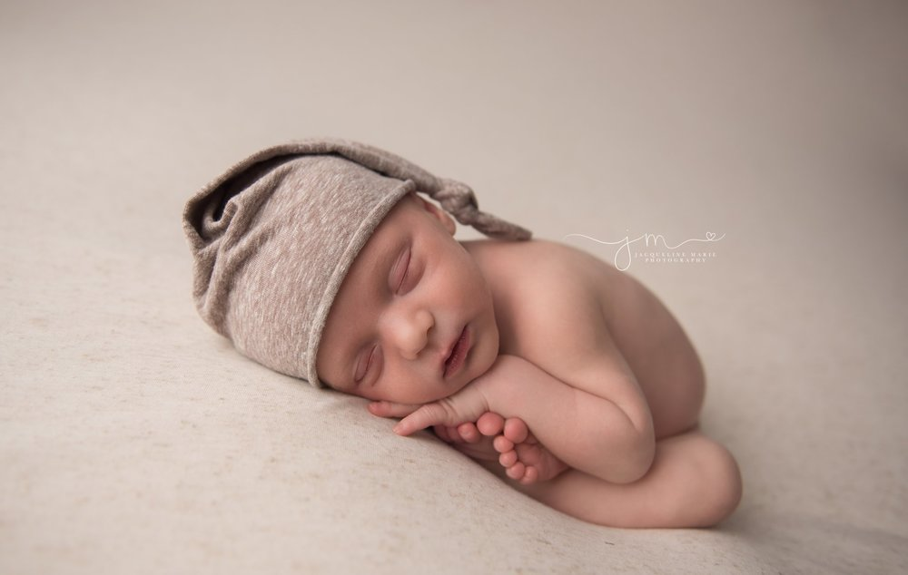 newborn baby boy wears tan sleepy hat while curled up on cream blanket for newborn  pictures in columbus ohio