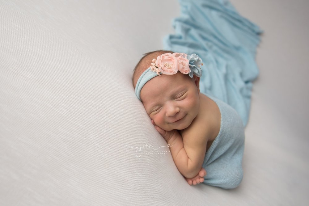 columbus ohio newborn baby smiles is wrapped in light blue wrap and smiles for newborn pictures