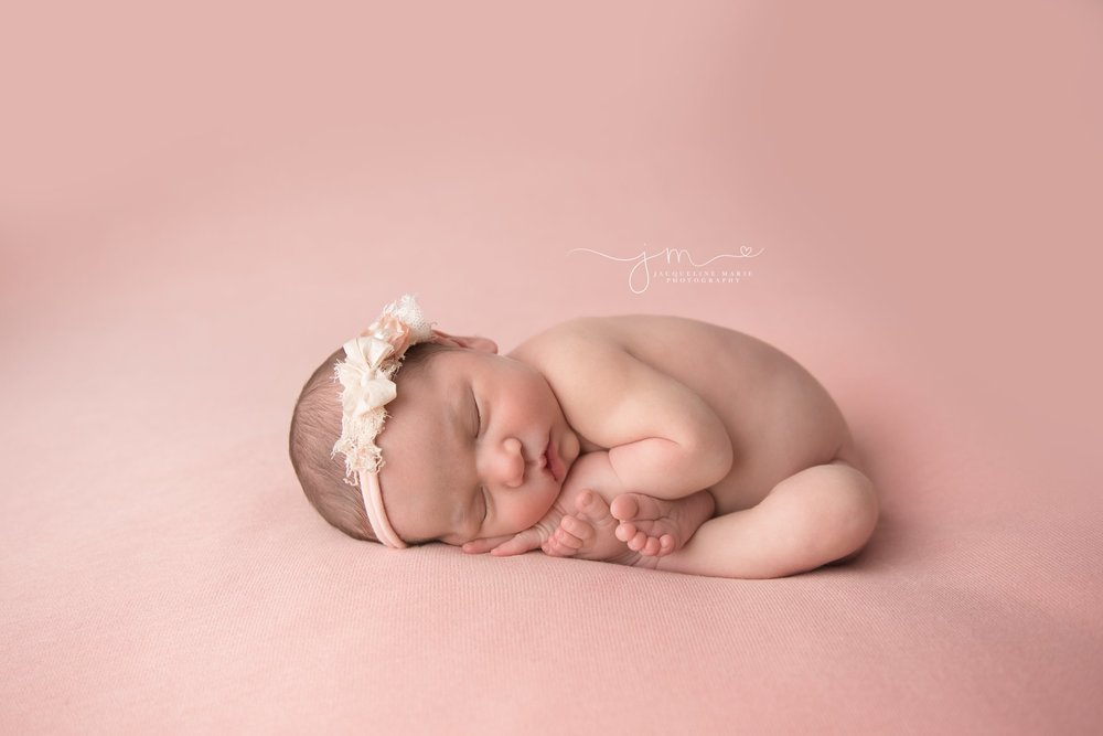 columbus ohio newborn baby girl sleeps while curled in taco pose at newborn photography studio