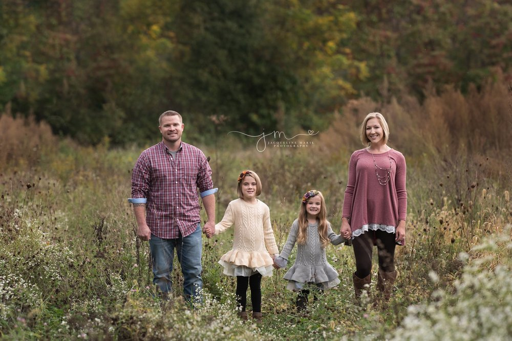 family of four from pickerington ohio holds hands and smiles in a field during their fall family photography session
