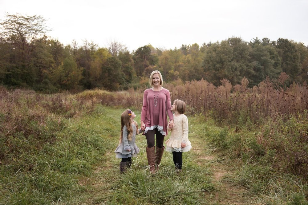 mother and two daughters wear ruffle sweaters for their outdoor fall family photography session in Columbus ohio