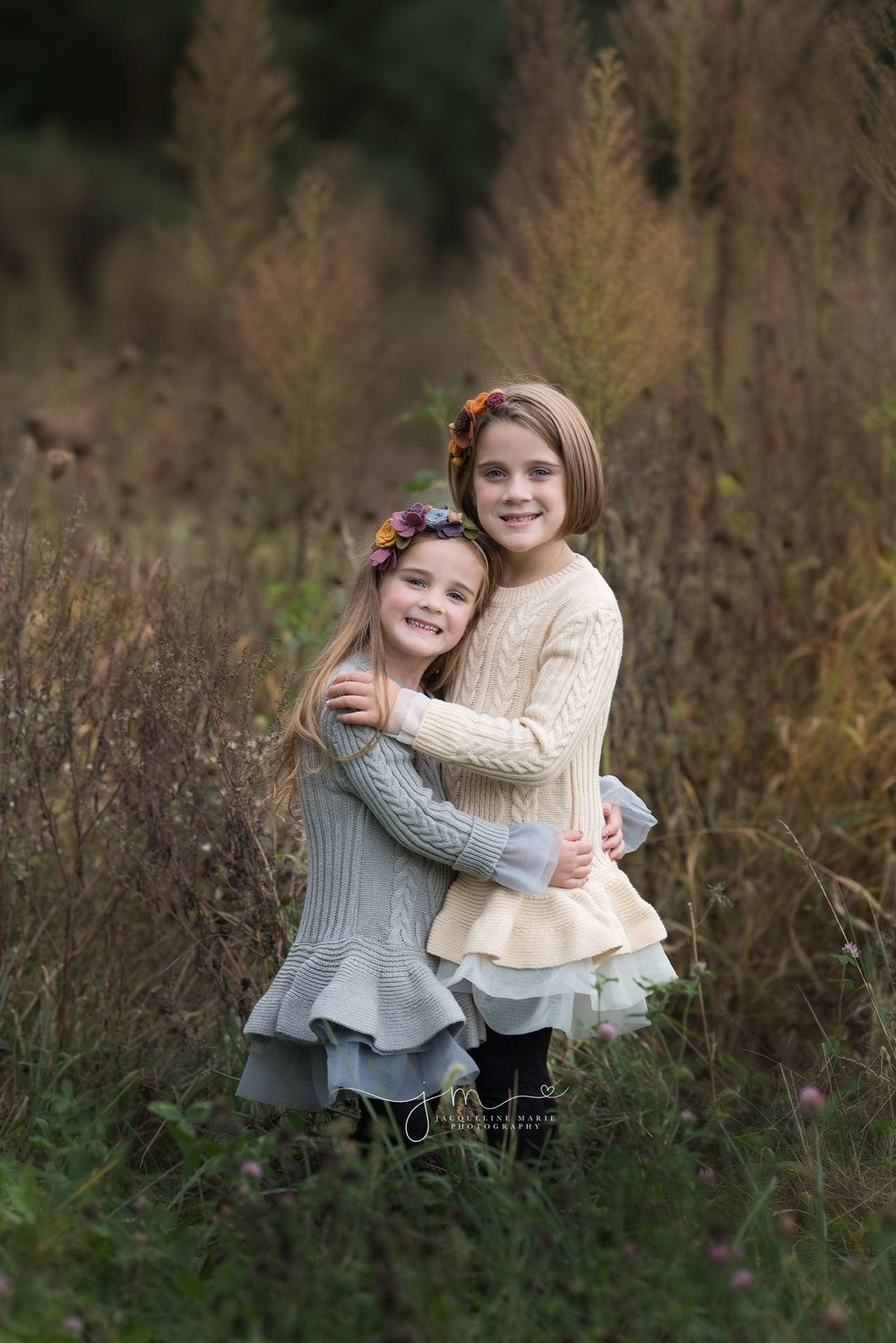 best family photographer in columbus ohio features image of sisters hugging in a fall field of tall grass