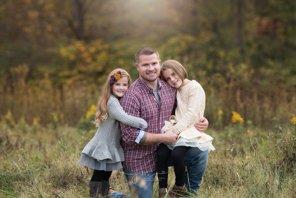 father kneels and hugs daughters for outdoor fall family photography in columbus ohio