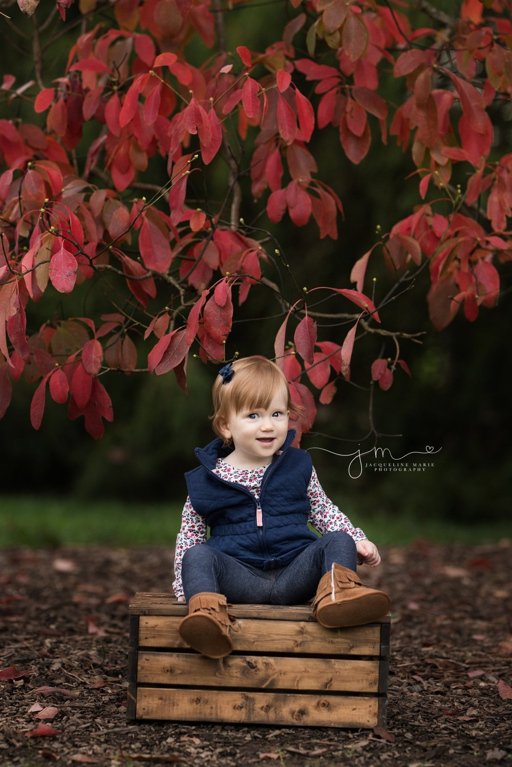 toddler girl sits on wooden box and smiles in columbus ohio for outdoor portrait session