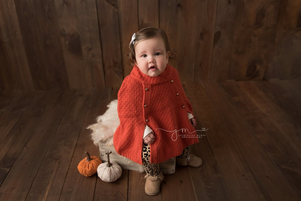 columbus ohio children and milestone photographer features image of little girl smiling with pumpkins