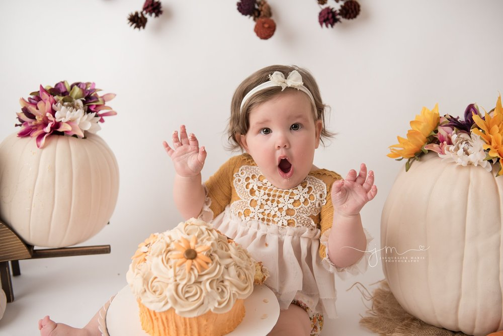 first birthday photographer in columbus ohio styles cake smash session with pumpkins and fall flowers