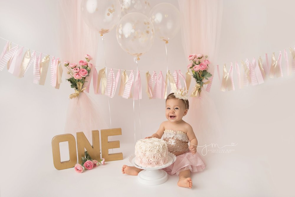 columbus ohio first birthday photographer styles pink and gold cake smash photography session with flowers and balloons