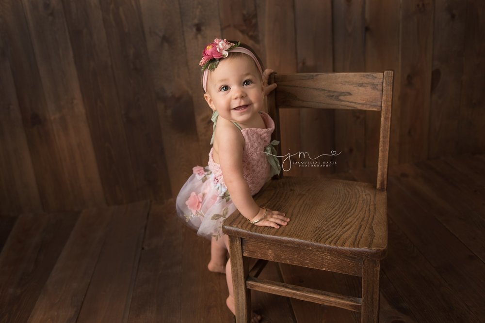 columbus ohio child and baby photographer features image of 1 year old standing at wooden chair while wearing pink and floral romper