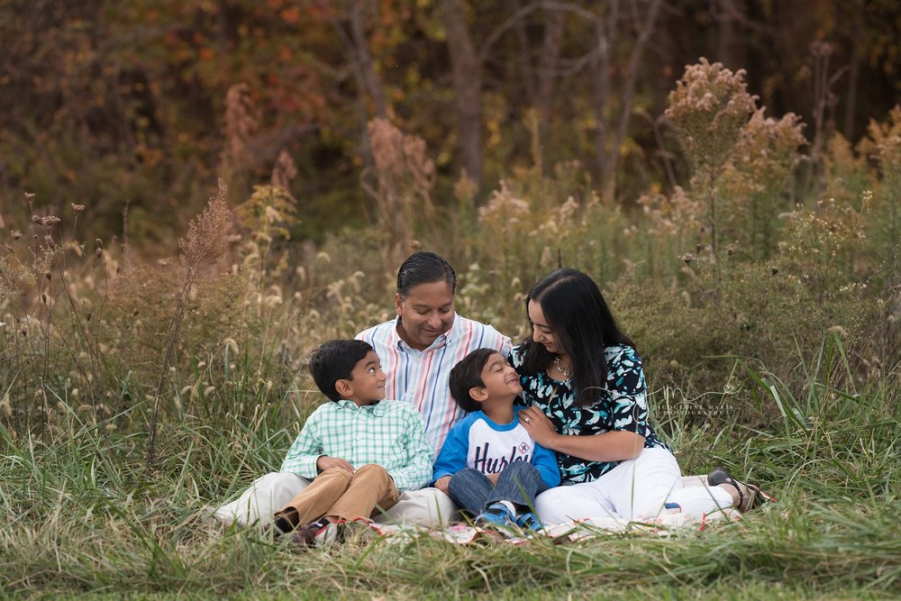 mother and father sit with their two sons and smile in a field of grass during their fall family portrait session in columbus ohio