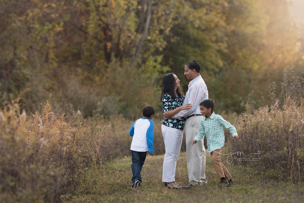 two children laugh and run around their parents during family portraits in columbus ohio
