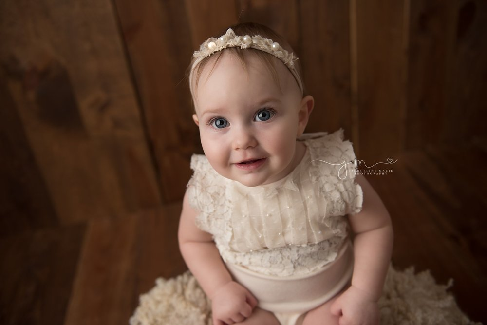 baby photographer in columbus ohio features images of baby on dark wood wearing a cream pearl romper