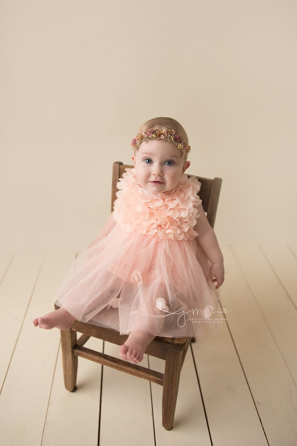 columbus ohio first birthday and baby photographer features image of baby girl in a wood chair wearing a pink dress