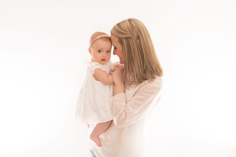 mother hugs and holds her daughter for 6 month milestone pictures with dream lighting in columbus ohio photography studio