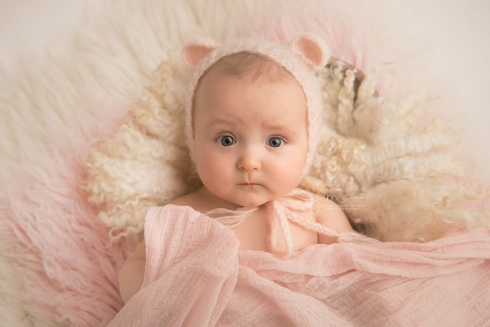 6 month old baby girl wears pink bear bonnet for milestone pictures in columbus ohio