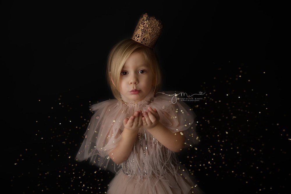 columbus ohio children photographer features image of three year old blowing gold glitter wearing pink dress for glitter mini photography session, glitter session with tutu du mode dresses