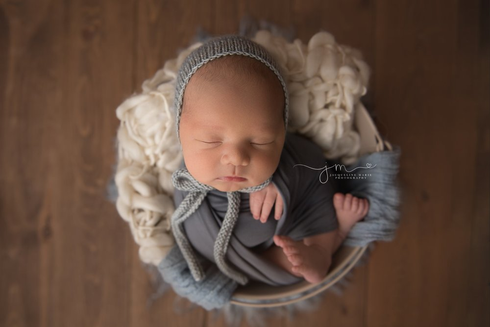newborn baby boy wears light blue bonnet while swaddled in blue wrap for newborn photography session in columbus ohio