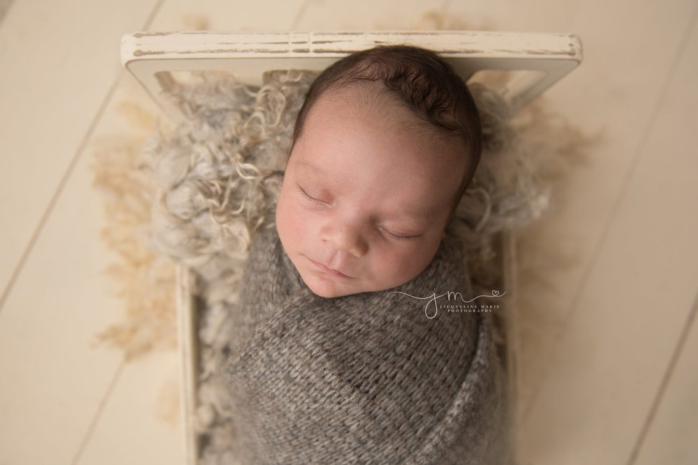 newborn photographer in columbus ohio swaddled baby boy in wooden bed for newborn session