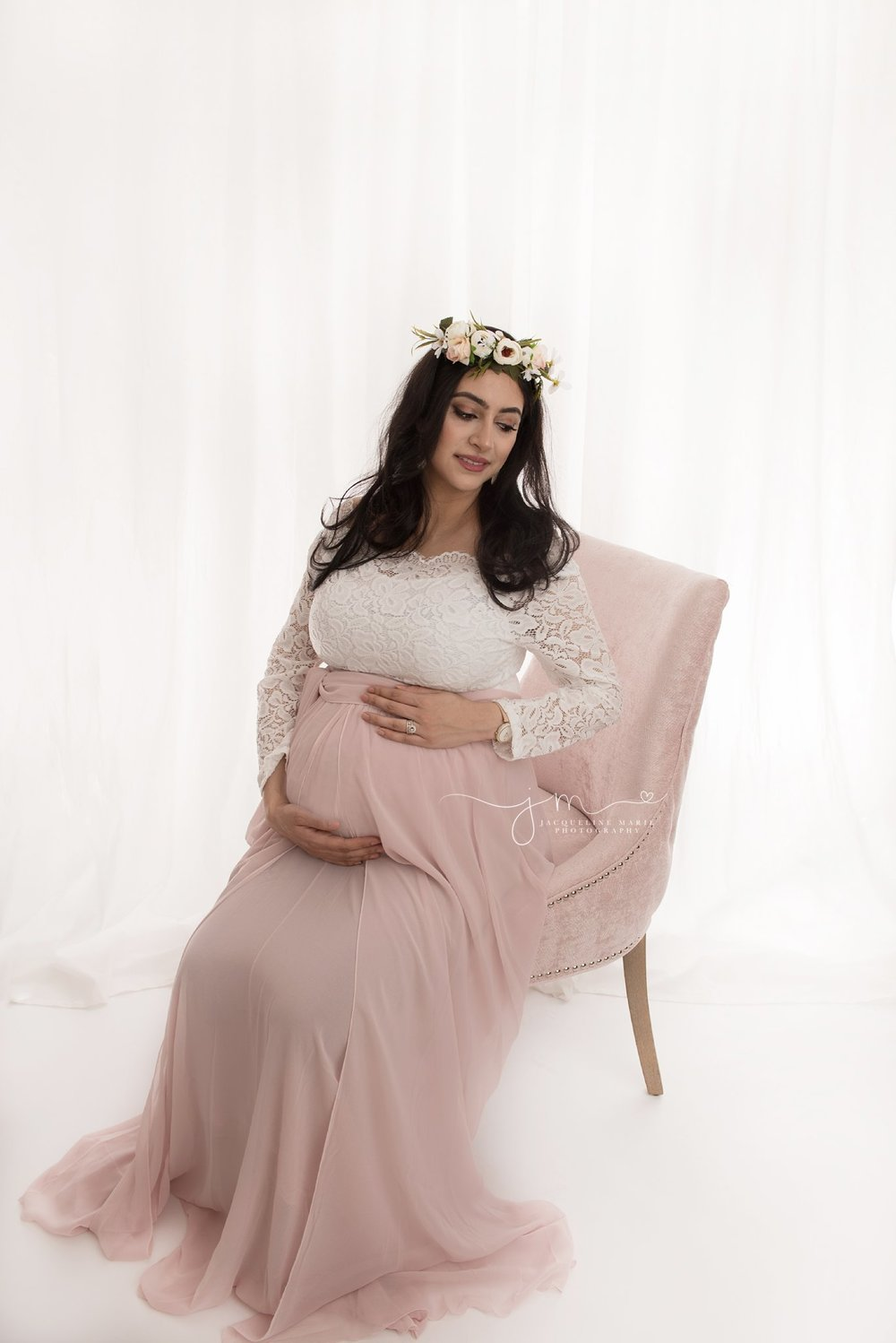 pregnanct mother sits on pink chair columbus ohio photography studio for maternity and pregnancy pictures