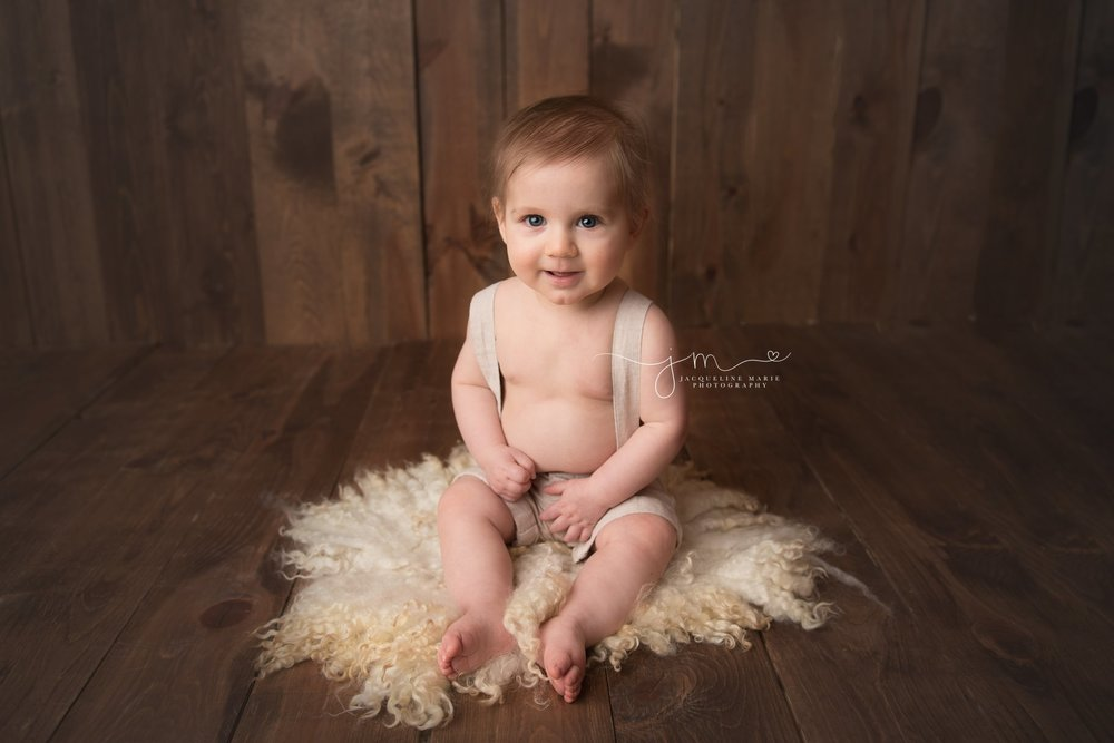 6 month old baby boy wears khaki overalls while smiling for milestone baby session in columbus ohio