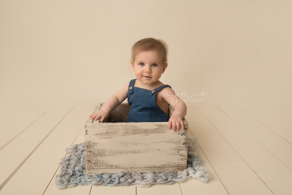 6 month old boy wears blue romper while sitting in cream wood prop box in columbus ohio