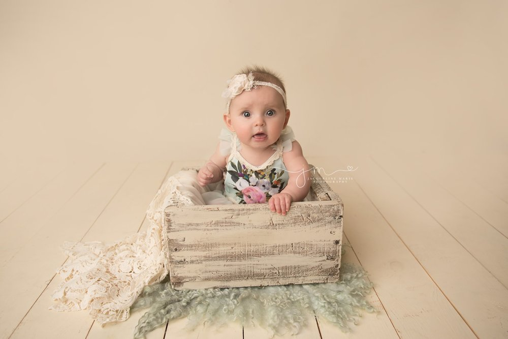 6 month old baby girl wears floral romper and matching headband for milestone baby pictures in columbus ohio