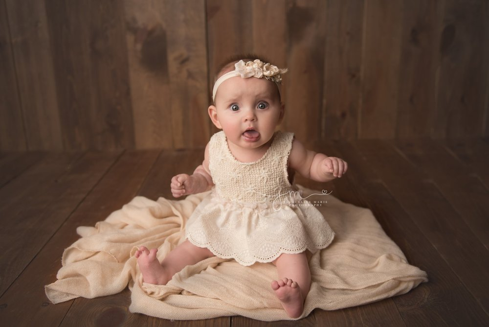 columbus ohio 6 month old baby girl sits up for milestone baby pictures wearing cream romper