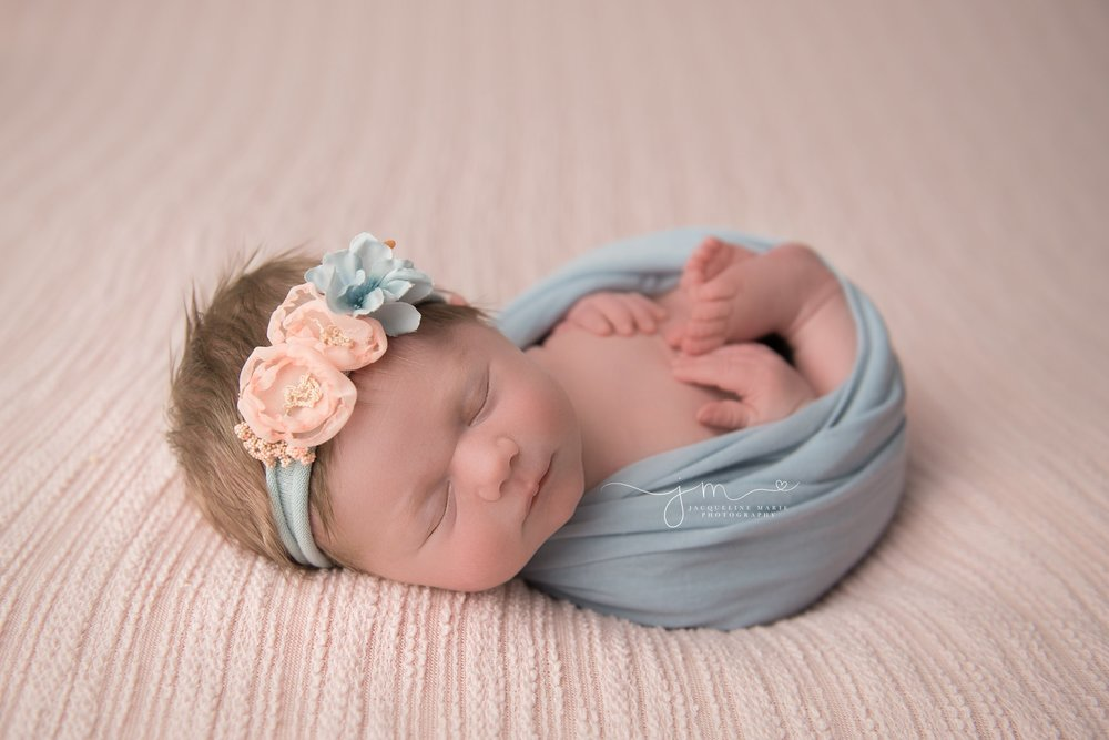 newborn baby girl wrapepd in blue wrap with matching headband in columbus ohio newborn photography studio