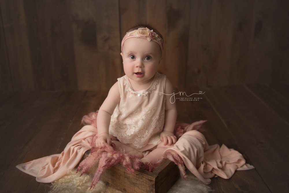6 month old baby girl wears pastel pink romper and matching headband for baby milestone pictures in columbus ohio
