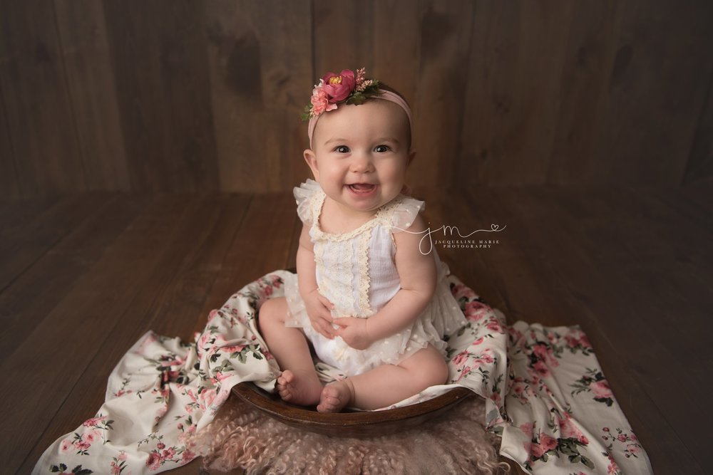 columbus ohio baby photographer poses baby girl in wood bowl with floral wrap and pink headband