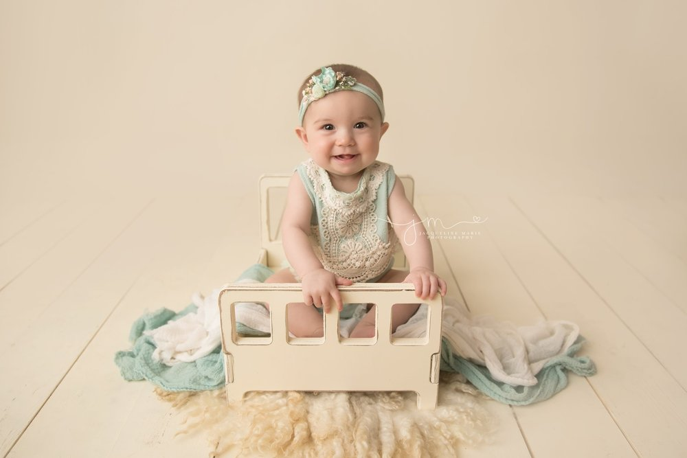 columbus ohio baby girl sits on cream wood bed for milestone photography session and smiles