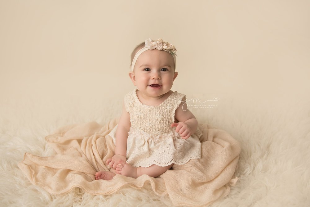 scarletts wears cream lace romper and matching headband for 6 month milestone photography session in columbus ohio