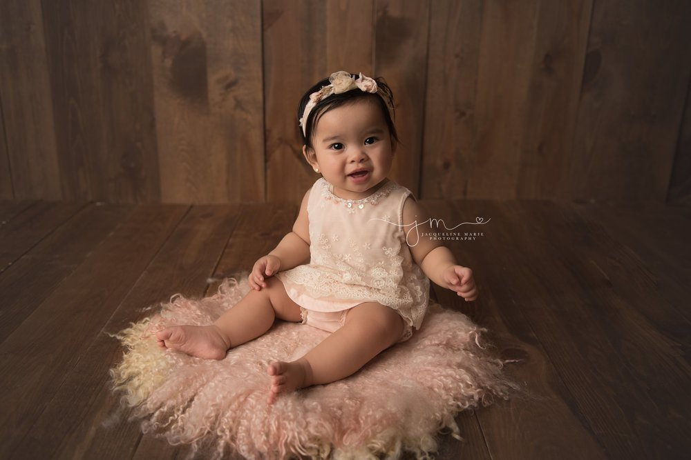 columbus ohio baby girl smiles for studio birthday session wearing pink romper and floral headband
