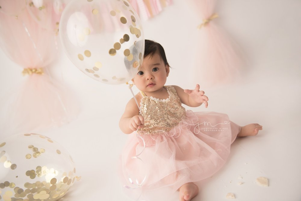 1 year old holds gold confetti balloon for first birthday cake smash session in columbus ohio