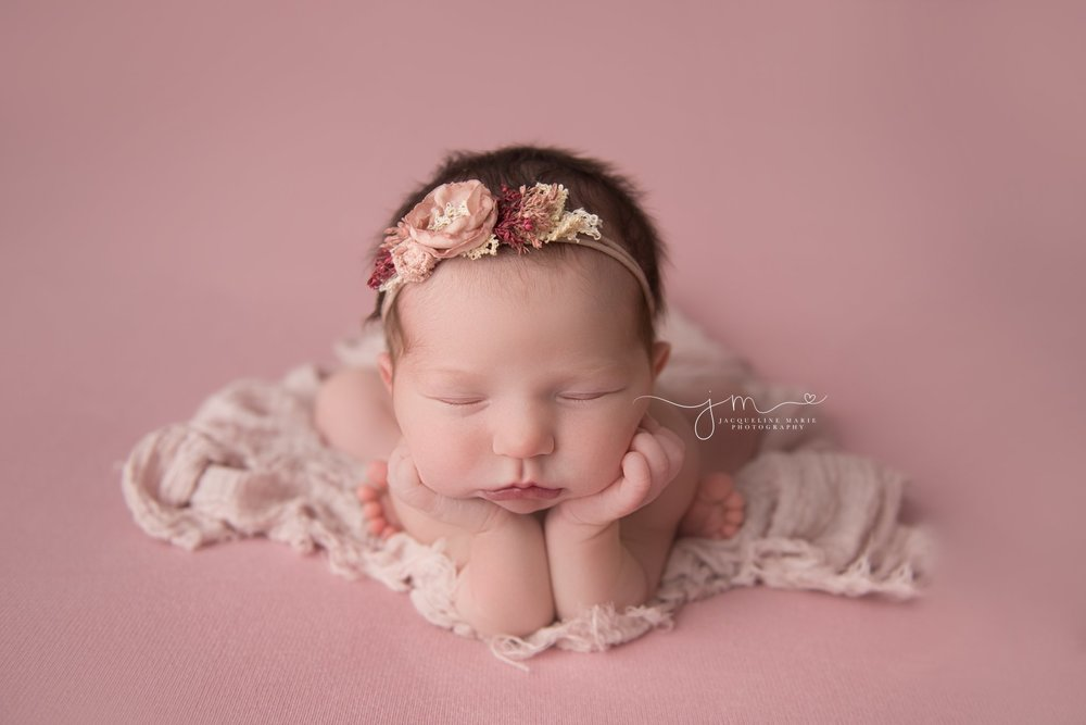 columbus ohio newborn baby girl wears pink floral headband for newborn pictures