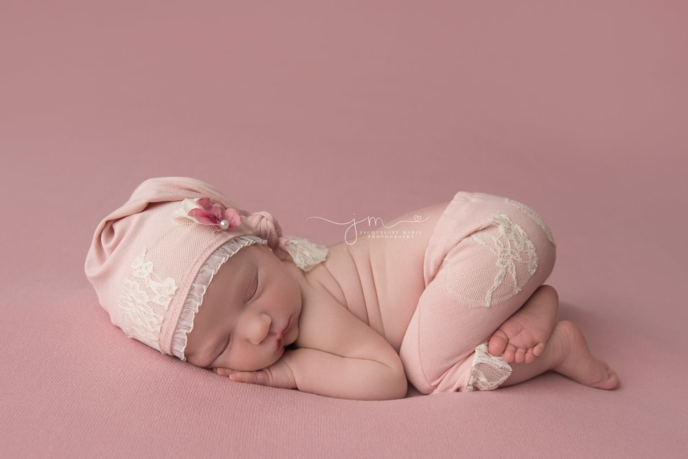 newborn baby girl wears pink sleepy hat and pants for newborn pictures in columbus ohio newborn studio