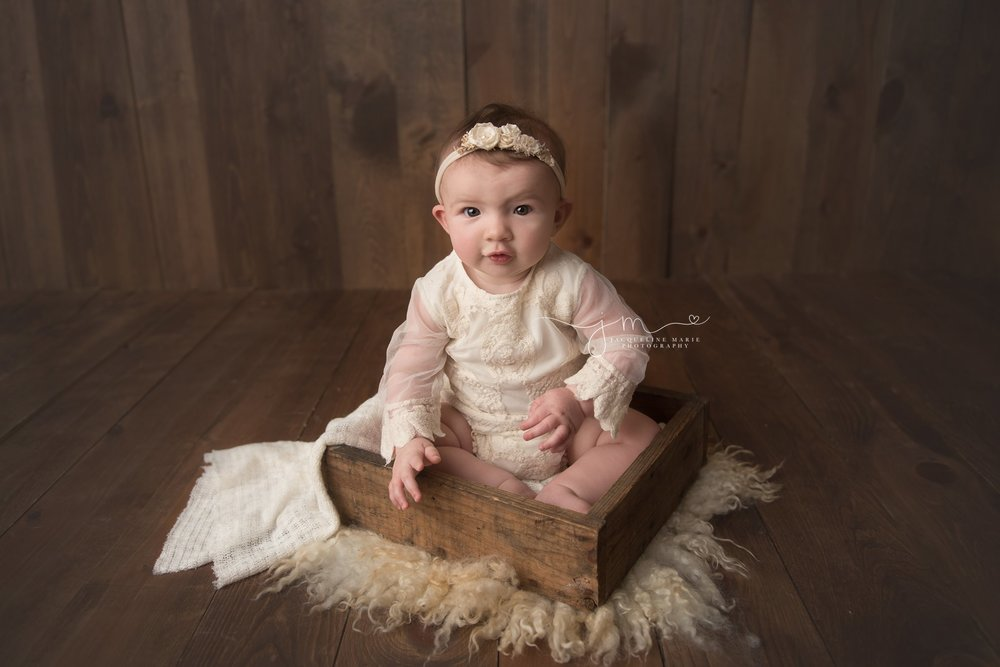columbus ohio baby girl wears cream lace romper while sitting in wood prop box for milestone pictures
