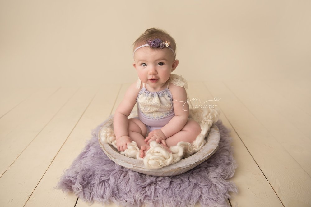 5 month old baby girl wears lilac and lace romper for baby pictures in columbus ohio studio